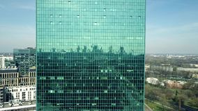 Aerial shot of an office building green tinted mirror facade reflecting cityscape. Aerial shot of an office building green tinted mirror facade reflecting city Royalty Free Stock Image