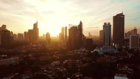Aerial shot of office buildings at sunset. Jakarta - Indonesia. January 23, 2018: Beautiful aerial shot of office buildings at sunset time from a drone flying stock video