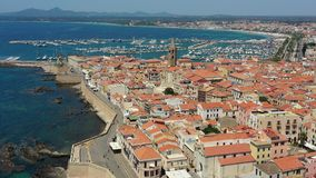 Aerial shot over Alghero old town, cityscape view on a beautiful day with harbor and open sea in view. Alghero, Italy. Panoramic stock footage