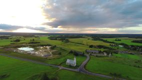 Aerial shot over lush green fields and meadows. Sunset. stock footage