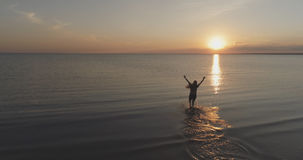 Aerial shot over teen girl barefoot running and raising arms in water on baltic sea beach in sunset time Royalty Free Stock Photos