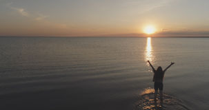 Aerial shot over teen girl barefoot running and raising arms in water on baltic sea beach in sunset time Stock Photo