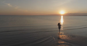 Aerial shot over teen girl barefoot running in water on baltic sea beach in sunset time Stock Photo