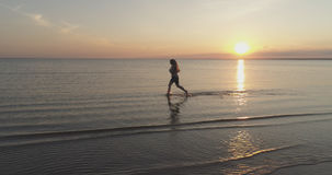 Aerial shot over teen girl barefoot running in water on baltic sea beach in sunset time Stock Image