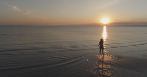 Aerial shot over teen girl barefoot running in water on baltic sea beach in sunset time Stock Photography