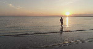 Aerial shot over teen girl barefoot stand in water on baltic sea beach in sunset time Royalty Free Stock Photo