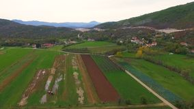 Aerial shot over village with houses and green valleys. Countryside view in foreground and mountains in background stock footage