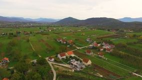 Aerial shot over village with houses and green valleys. Countryside view in foreground and mountains in background stock video footage