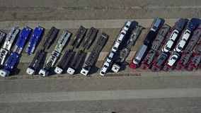 Aerial shot of parked car transporter trucks and trailers, top view. 4K video stock footage
