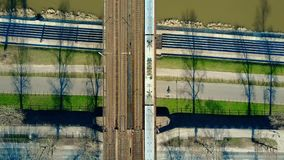 Aerial shot of passenger train moving on railway bridge across the river and bicycle road, top view. Ecologic Stock Photo
