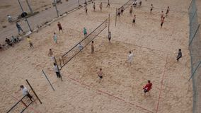 Aerial shot people compete beach volleyball at sand sports ground on sunny day stock video footage
