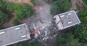 Aerial shot of pulling down the building by means of machinery