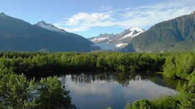 Alaska lake in a forest with mountains in the background stock video