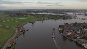 Aerial shot of river with windmills and township, Netherlands stock footage
