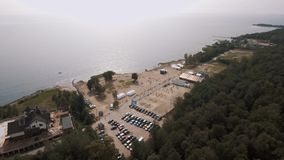 Aerial shot sandy beach on sea shore with white tents and sports ground stock footage