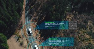 Aerial shot of self Driving trucks driving on a forest highway