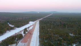 Aerial shot of semi truck on a dirt road in background on clear winter landscape. Aerial view of lorry on a gravel road in background on clear winter landscape stock video