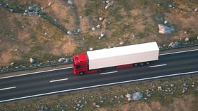 Semi-trailer truck driving along a desert road. Aerial shot of a semi truck driving on a highway into the sunset. Realistic high quality 3d animation.n stock video