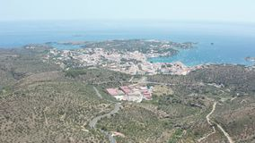 Drone view of Cadaques, town among mountain hills. Aerial shot of serpentine road to Cadaques on Cap de Creus peninsula against background of beautiful seascape stock video footage