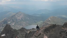 Aerial shot of silhouette of a man climbing to the top of the mountain.