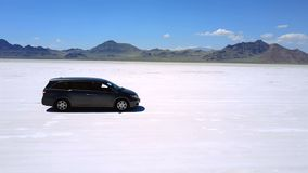 Aerial shot of silver minivan car standing in the middle of Bonneville salt lake desert flats, drone making sharp moves. stock video footage