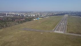 Aerial shot of a small propeller airplane flying near city airport runway on a sunny day Stock Photos