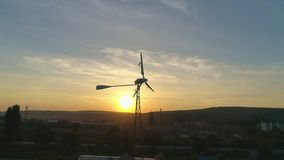 Aerial shot: Small Wind Turbin over a sunset background. loop. Alternative renewable energy production. 4k stock footage