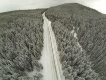 Aerial shot of snow-covered road in the countryside Carpathian Mountains Royalty Free Stock Image