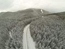 Aerial shot of snow-covered road in the countryside Carpathian Mountains Royalty Free Stock Photography