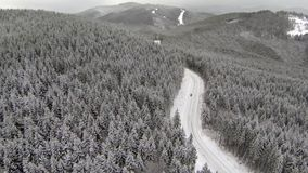 Aerial shot of snow-covered road in the countryside Carpathian Mountains stock video