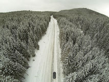 Aerial shot of snow-covered road in the countryside Carpathian Mountains with car on way Stock Photo