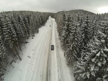Aerial shot of snow-covered road in the countryside Carpathian Mountains with car on way Stock Photography