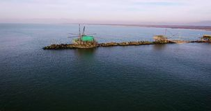 Aerial shot of some fishermen houses with huge nets outside situated in the middle of the sea, in Tuscany, Italy stock video