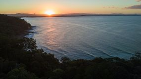 Aerial shot of the sun setting above the coast line around Noosa in the Sunshine cost stock images