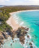 Aerial shot at sunrise over the ocean and white sand beach with swimmers and surfers enjoying summer stock images