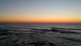 Aerial shot at sunset over dark ocean with beautiful blue orange gradient sky in Portugal. As waves crash against black rocks below stock video