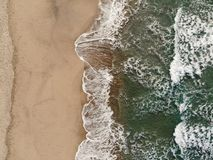 Epic Vertical aerial drone view of waves motion on multicolored sandy beach royalty free stock images