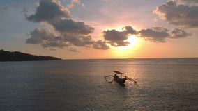 Aerial shot of three fisherman`s boat in a sea at sunset time. Drone moves to the left.  stock footage