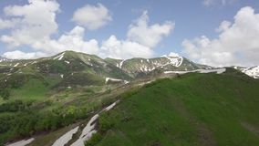 Aerial shot of tops of green mountains with small snow spots stock video footage