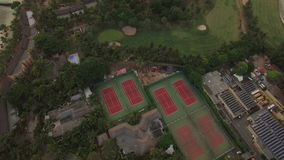 Aerial shot of town on the island and blue ocean, Mauritius. Aerial view of town with houses and tennis courts on the peninsula of Mauritius with following view stock video footage