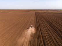Aerial shot of a tractor cultivating field at spring. Agricultural activity Royalty Free Stock Photos