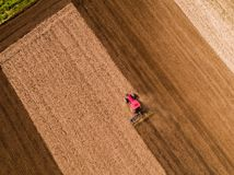 Aerial shot of a tractor cultivating field at spring. Agricultural activity Stock Photography