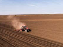 Aerial shot of a tractor cultivating field at spring. Agricultural activity Royalty Free Stock Images