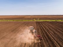 Aerial shot of a tractor cultivating field at spring. Agricultural activity Stock Images