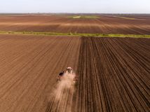 Aerial shot of a tractor cultivating field at spring. Agricultural activity Royalty Free Stock Image