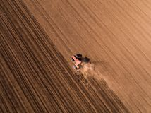 Aerial shot of a tractor cultivating field at spring. Agricultural activity Royalty Free Stock Photo