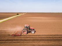 Aerial shot of a tractor cultivating field at spring. Agricultural activity Royalty Free Stock Photography