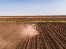 Aerial shot of a tractor cultivating field at spring. Agricultural activity Stock Photos