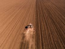 Aerial shot of a tractor cultivating field at spring. Agricultural activity Stock Image