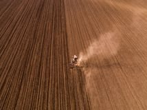 Aerial shot of a tractor cultivating field at spring. Agricultural activity Stock Photo